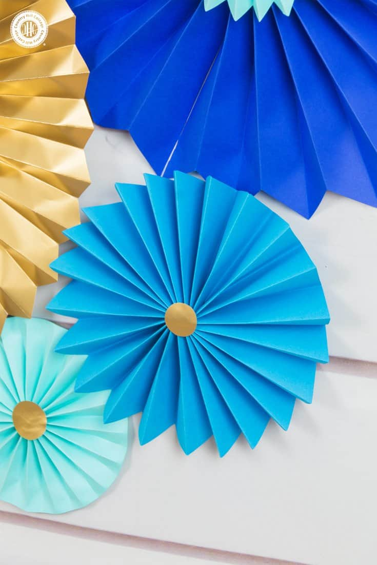 Learn to craft beautiful paper rosettes with card stock or wrapping paper! ! They are stunning for parties and weddings, or as wall ornaments. #DIY #papercrafts | countryhillcottage.com
