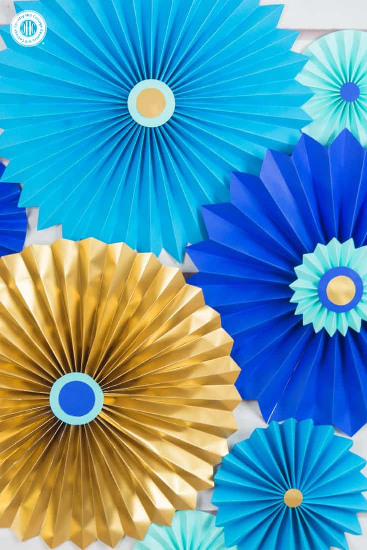 Learn to craft beautiful paper rosettes in our quick and easy paper craft DIY tutorial! They are stunning for parties and weddings, or as wall ornaments. #DIY #papercrafts | countryhillcottage.com