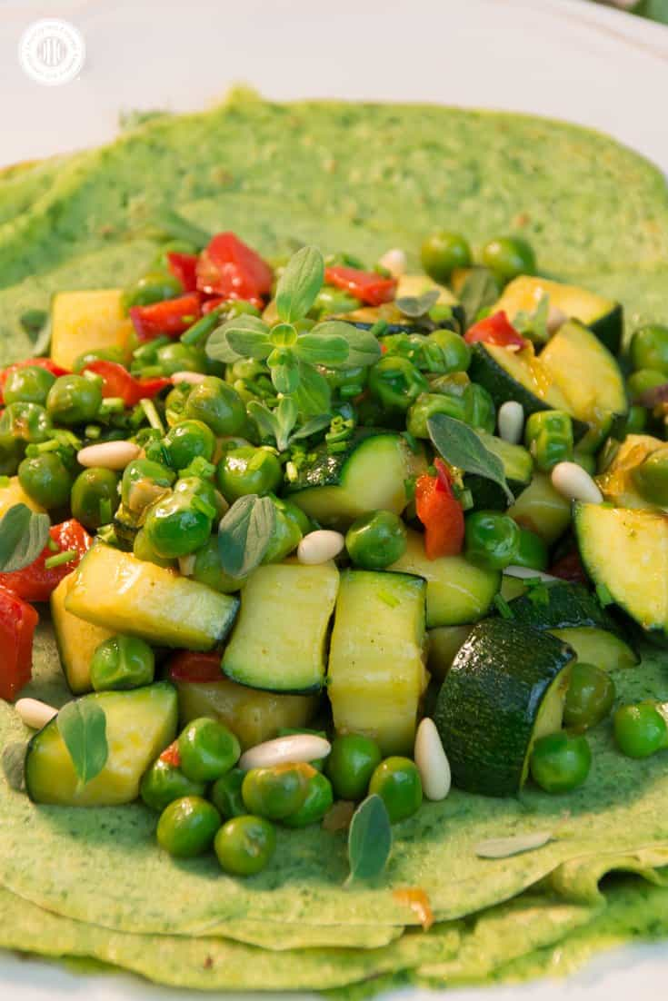 Healthy greens shine in these colourful spinach parsley crepes with stir-fried vegetables that include zucchini, peas and pepper. The veggies are delicious alone, and even better served on these delicious spinach parsley crepes and topped with toasted pine nuts and fresh marjoram. #crepes #stirfry #vegetarian| countryhillcottage.com