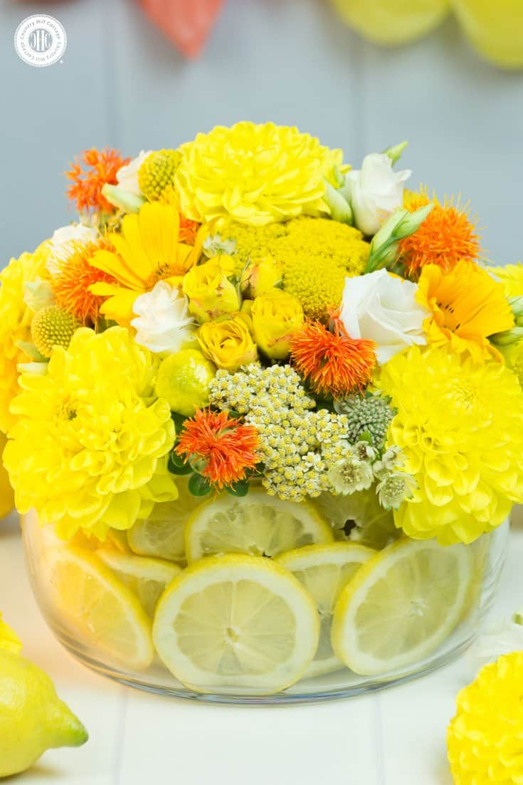 Learn to make a stunning yellow centrepiece with lemons! Lemons add a pop of colour and visual interest plus hide the floral foam that holds the flowers. #flowerarrangement #lemons #centerpiece | countryhillcottage.com