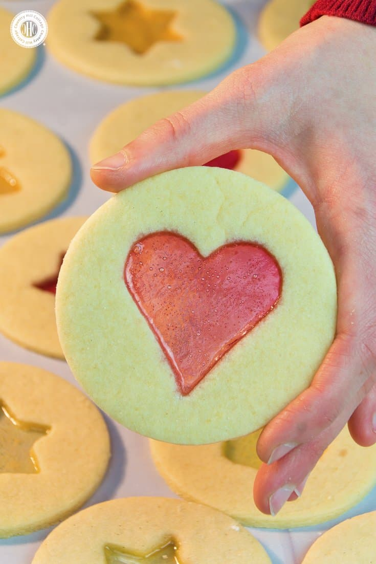 We've rounded up 10 easy Mother's Day treat ideas to celebrate Mum like these heart window cookies. Our list of homemade food gifts and Mother's Day sweets includes biscuits, truffles, cupcakes, mini cakes, fondant fancies, and delicious strawberry jam. Each recipe comes with free printable labels or treat boxes, giving you everything you need to create a special present that Mum can cherish. #mothersday #foodgifts #giftgiving #cookies #prinatbles | countryhillcottage.com