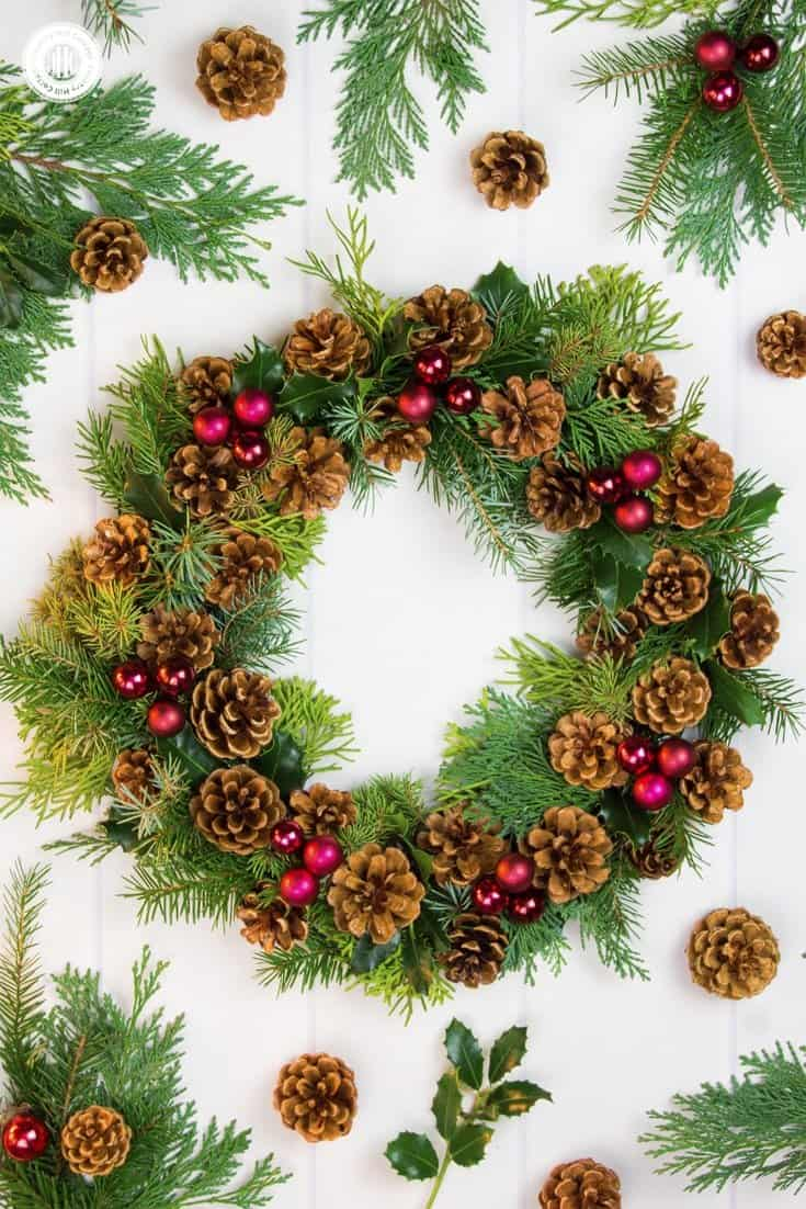 Handmade wreaths are a wonderful way to spread some holiday cheer to your loved ones. This classic red and green pinecone wreath is made with pinecones, spruce, conifer twigs, holly leaves, and red mini bauble ornaments. Check out the tutorial and get creative! #Christmas #flowerarranging #wreath | countryhillcottage.com