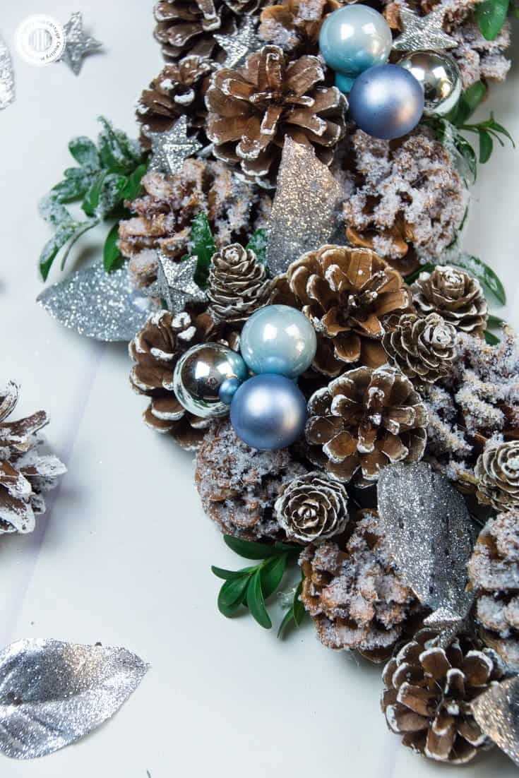 """Nothing says """"Happy Holidays"""" like a handcrafted wreath. We've created a gorgeous icy winter pinecone wreath that is as fun to create as they are to send! The wreath is made with frost-tipped pinecones, blue ornaments, iced boxwood, silver leaves and glittery stars. #Christmas #flowerarranging #wreath 