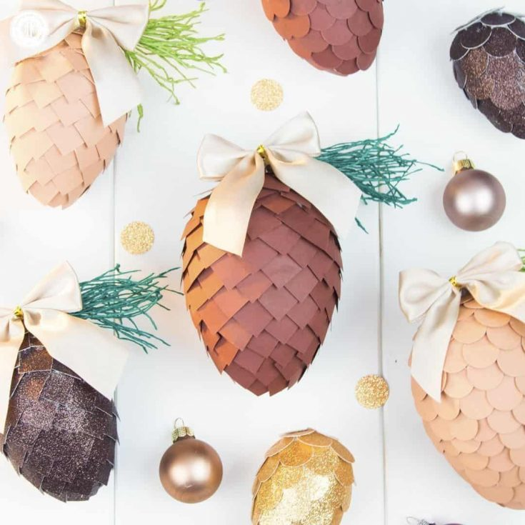 Learn how to make paper pinecone ornaments that you can use to decorate your Christmas tree or for packaging gifts. The ornaments are made by applying small paper squares or circles on polystyrene eggs. You can choose any size of egg shape and use a wide variety of papers for the scales, such as cardstock, scrapbook paper, glitter paper, or gift wrap. We also demonstrate how to make pine needles form crepe paper to decorate the ornaments. #DIY #pinecone #papercrafts   countryhillcottage.com