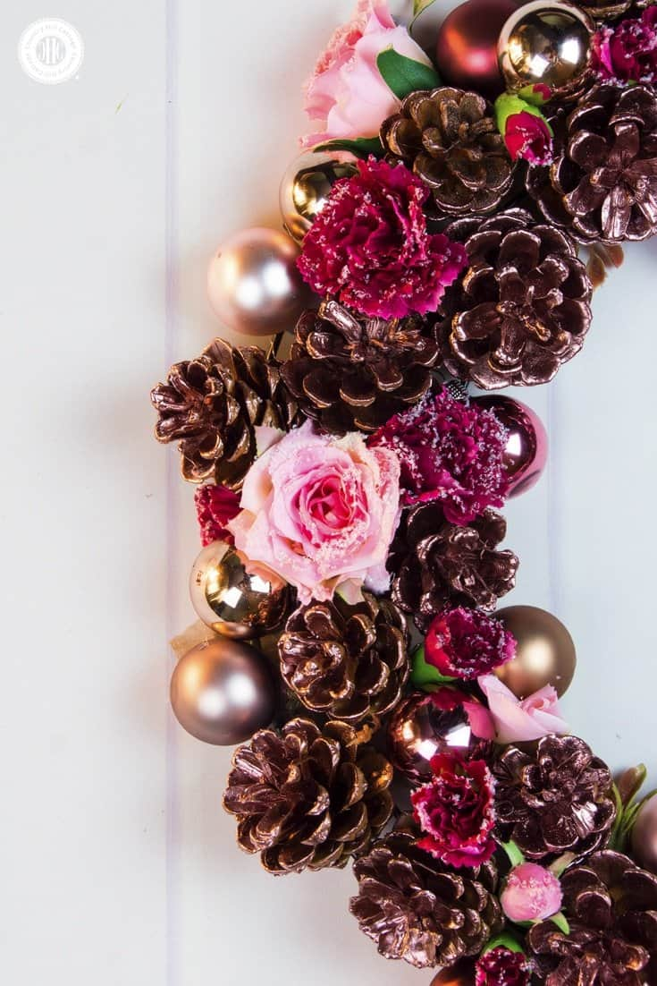 Our romantic rose gold pinecone wreath is such a simple and fun way to add some style to your home this holiday season. All you need are some pinecones, silk flowers, mini bauble ornaments, and rose gold spray paint your good to craft! #Christmas #flowerarranging #wreath | countryhillcottage.com