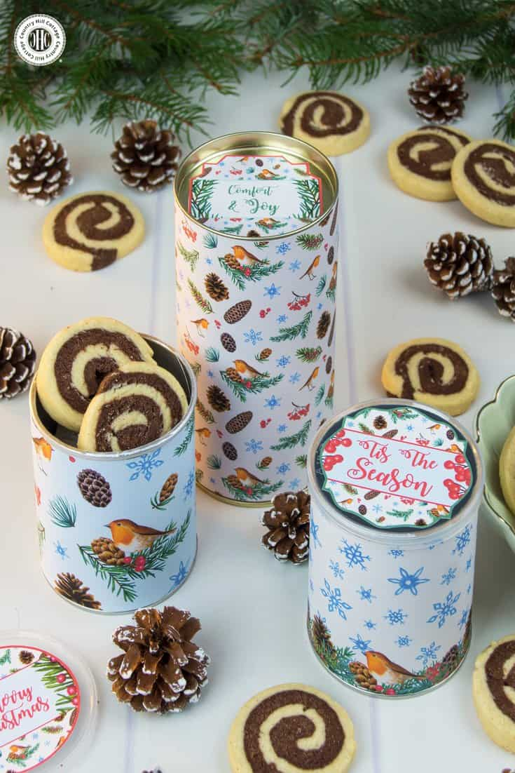 Festive upcycling at its finest! Repurpose empty cookie or crisp canisters into a gorgeous cookie giftable. Glue sheets of decorative pattern to the tins (cans). This process is even easier when you print the pattern on self-adhesive paper. We also used gift tags to decorate the lids. Get this and 10 more cookie packaging ideas! #Christmas #foodgifts #cookiepackaging #freebie | countryhillcottage.com