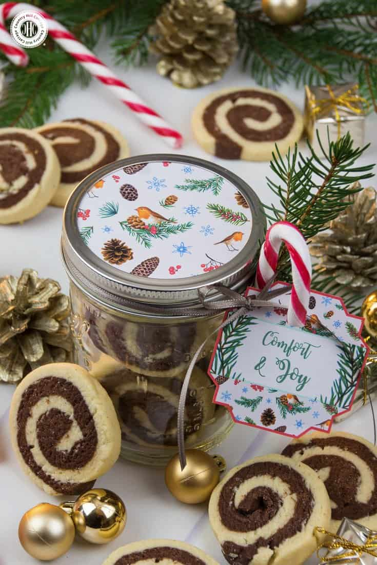 Put your cookies on display in shiny mason jars. We decorated the lid with a circle cut of decorative pattern, and tied a gift tag, candy cane, and twig to the jar. Get this and 10 more cookie packaging ideas! #Christmas #foodgifts #cookiepackaging #freebie | countryhillcottage.com