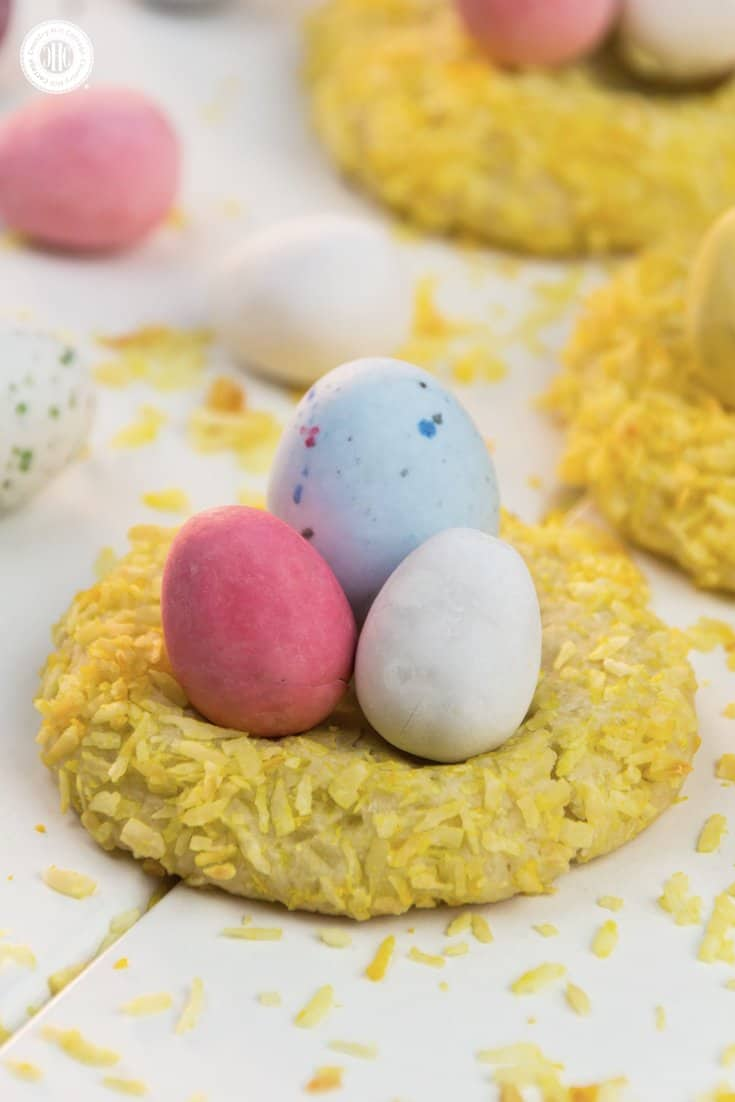 Easter nest cookie are a sweet treat for spring and Easter. . They consist of delicious cookie dough, rolled in coconut and stuffed with mini candy eggs. This recipe is great to do with kids. #Easter #spring #biscuits #cookies #bunnybiscuits #Easternest #Eastercookies #recipe #foodgift #giftgiving | countryhillcottage.com