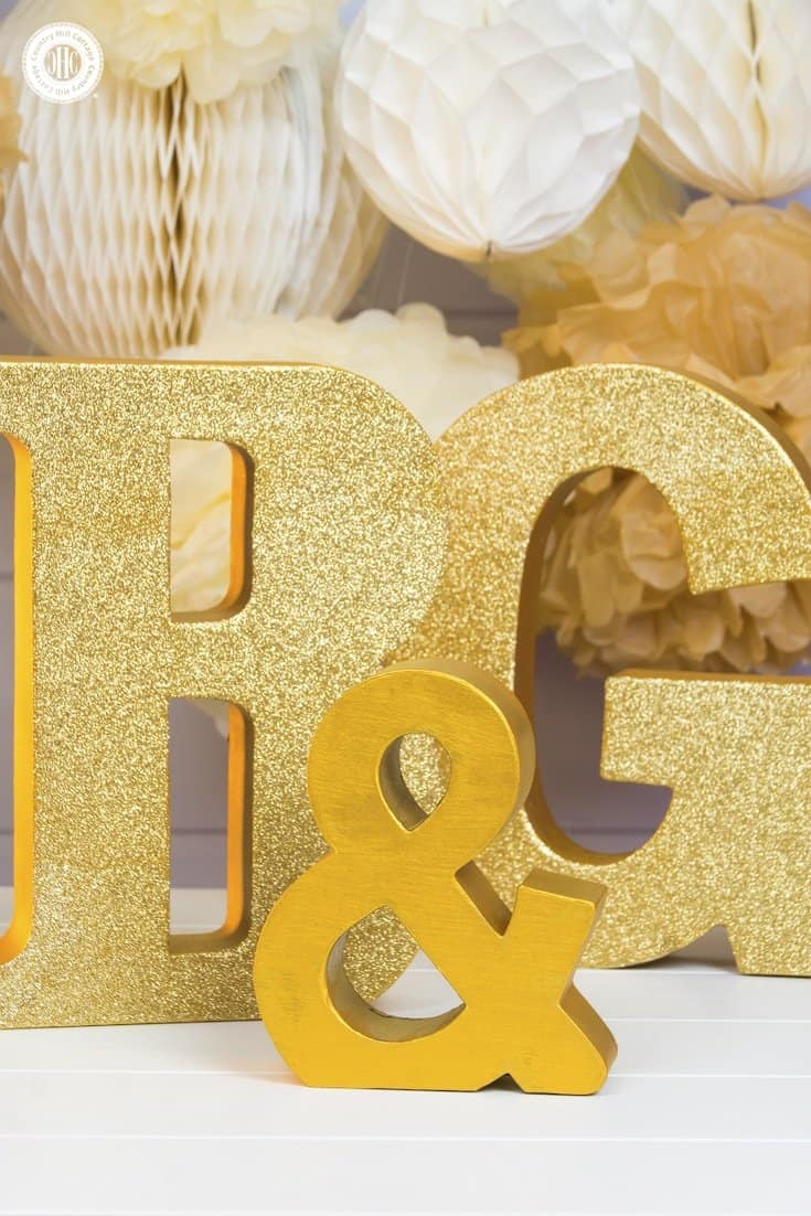 Learn how to make glitter wedding letters! We use large paper mache letters and show different techniques to paint the letters, apply glitter and decorate them with silk flowers. Monogram letters make fabulous wedding décor to display the initials of the bride and groom. You can use them as table decoration or hang them as a wall ornament. #diy #wedding #decor #glitter #monogram | countryhillcottage.com