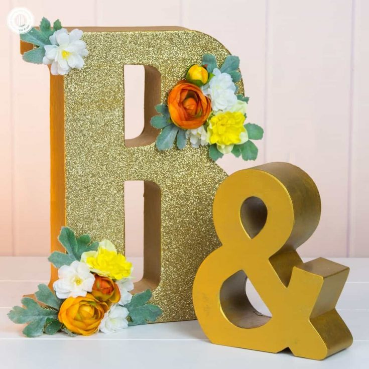 Learn how to how to make glitter wedding letters! We use large paper mache letters and show different techniques to paint the letters, apply glitter and decorate them with silk flowers. Monogram letters make fabulous wedding décor to display the initials of the bride and groom. You can use them as table decoration or hang them as a wall ornament. #diy #wedding #decor #glitter #monogram | countryhillcottage.com