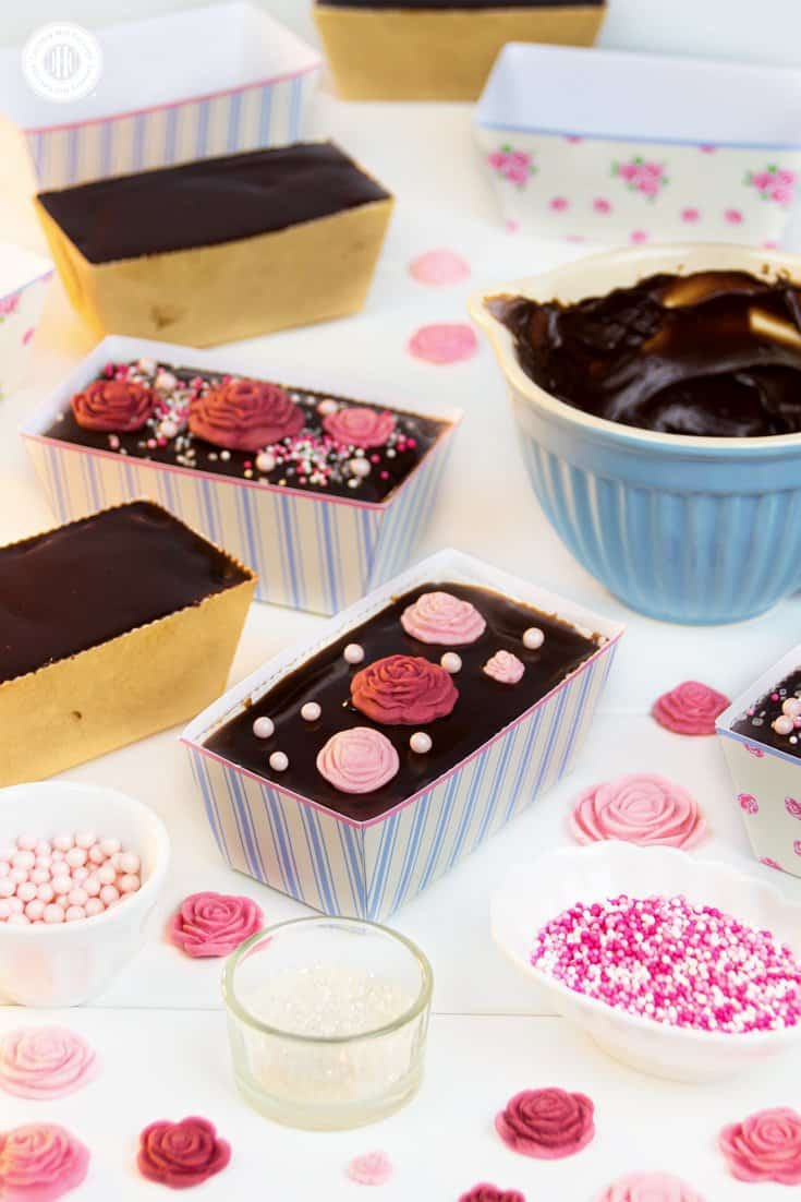 Rosewater tea cakes with a rich chocolate ganache glaze are the perfect treat to enjoy with a hot, strong cuppa, serve at a bridal shower, or gift to Mum on Mother's Day. The cakes are made with a quick one-bowl batter and topped with a rosewater-infused chocolate ganache. The loaves are decorated with edible sugar roses, and we put them in free printable loaf wrappers from our Vintage Rose collection. #rosewater #teacakes #cupcakes #chocolateganache #sugarroses   countryhillcottage.com