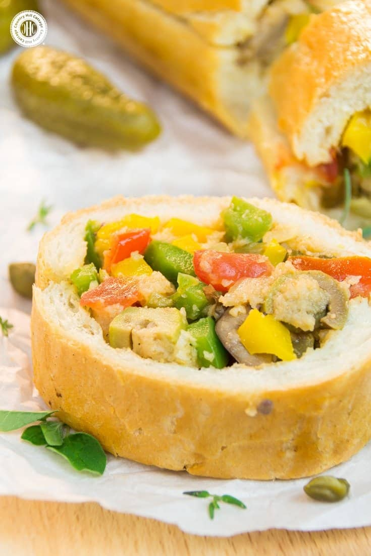 Ready for a new take on sandwiches? Then try Patafla, a delicious Mediterranean picnic loaf! Patafla is made with a French loaf (sounds scrumptious already, right?), and stuffed with a colourful summer veggie filling. Aside from being a terrific addition to your picnic basket, patafla also is a great party appetiser to feed a large crowd. #patafla #picnic #sandwich #recipe #tomatoes #peppers | countryhillcottage.com