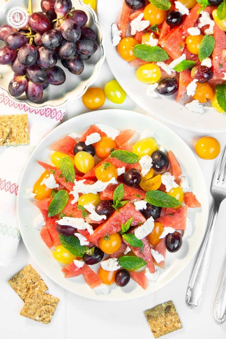 This quick and colourful watermelon salad is packed with fresh fruits and perfect to cool down on hot summer evenings. Aside from juicy watermelon slices, the recipe includes mozzarella cheese, cherry tomatoes and blue grapes, which add a burst of deep, rich sweetness. A lime vinaigrette with grapeseed oil adds zest to this light salad, while fresh mint leaves bring a fresh kick throughout. #watermelonsalad #watermelon #salad #grapes #mint #summersalad| countryhillcottage.com