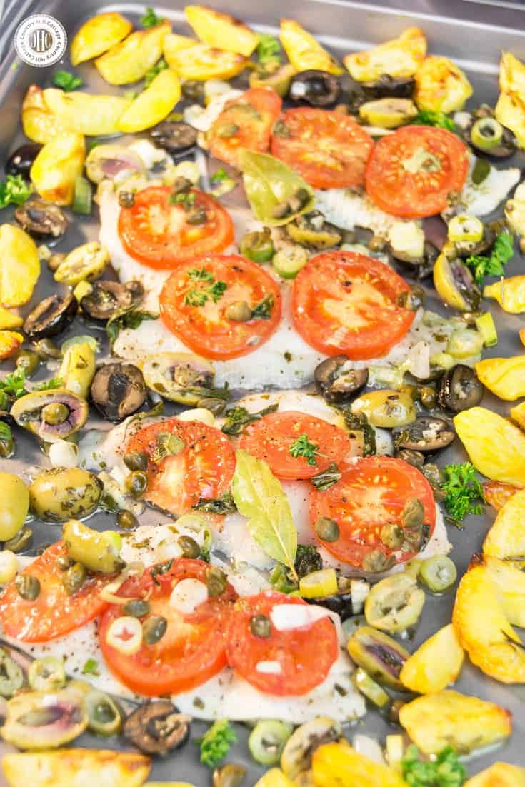 Baked Dover sole and veggies sheet pan combines two summer favourites: Dover sole and new potatoes. Dover sole is delicate in taste and texture and pairs perfectly with the aroma of juice tomatoes, spring onions, capers, olives, and fresh herbs. New potatoes are cut into wedges and pan-roasted as well. The recipe takes less than 1 hour, perfect for a quick midweek meal. It's also a great course of a light summer dinner. #sheetpandish #doversole #sole #fish #tomatoes| countryhillcottage.com