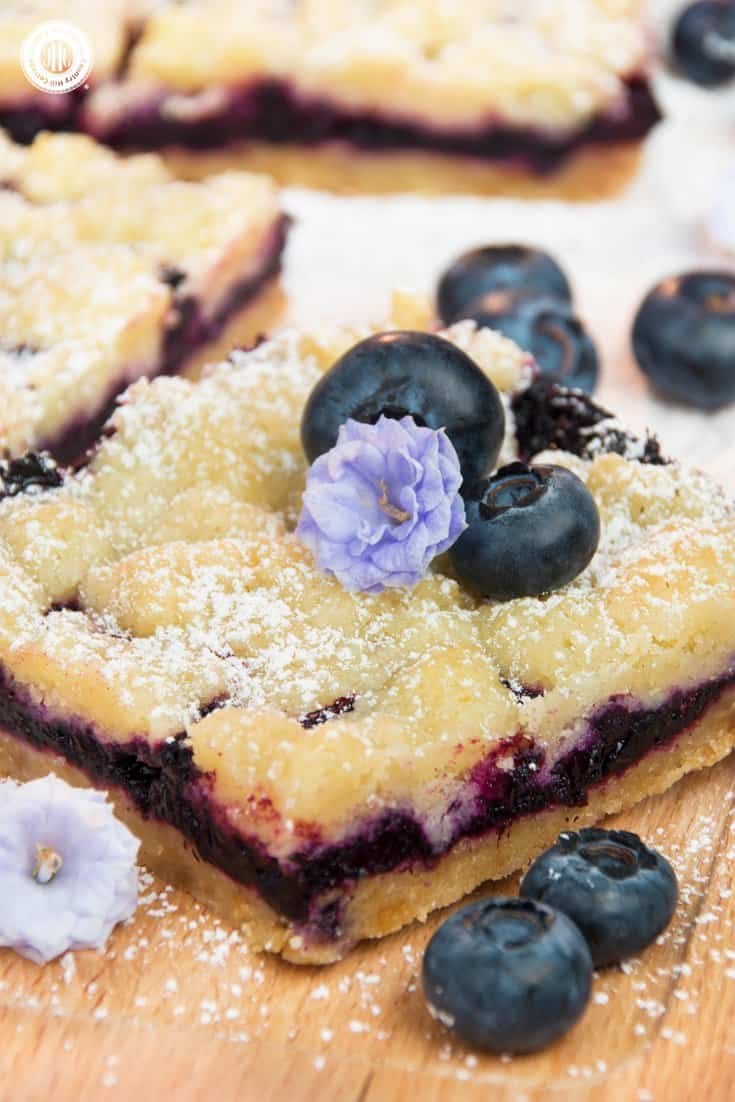 For a bite of pure bliss, sink your teeth into delicious blueberry streusel bars! Layers of crumbly streusel and sweet blueberry filling add up to a scrumptious bar cookie. The steps are incredibly simple, making it an easy-enough bake to get your kids involved. Instead of blueberries, you can also prepare the squares with frozen raspberries, blackberries, or quartered cherries. #blueberries #streusel #bars #bakingrecipe | countryhillcottage.com