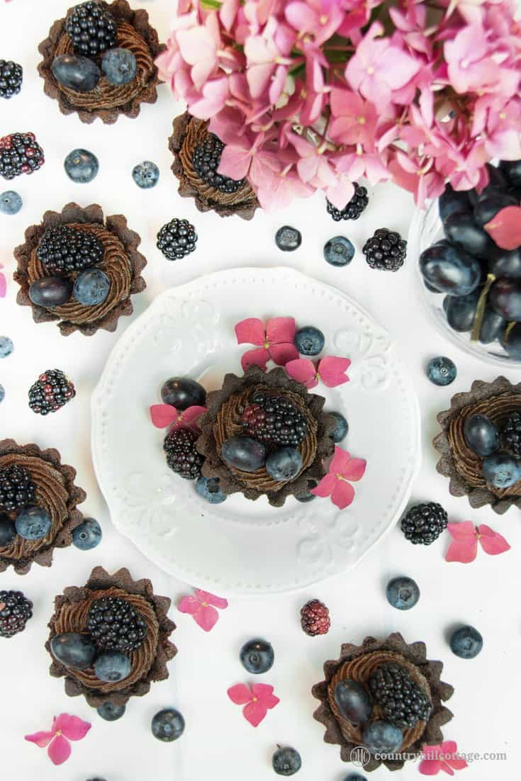 For a lovely afternoon tea indulgence bake delicious chocolate tartlets with berries! Crisp chocolate shells are laden with dark summer berries and filled with a delectable chocolate cream cheese filling with subtle berry notes. The dough is soft, crumbly and has an intense chocolate flavour. The soft filling is made with cream cheese, white and dark chocolate and blueberry jam to reflect the berry decoration. #tartlet #chocolate #tart #berries #bakingrecipe | countryhillcottage.com