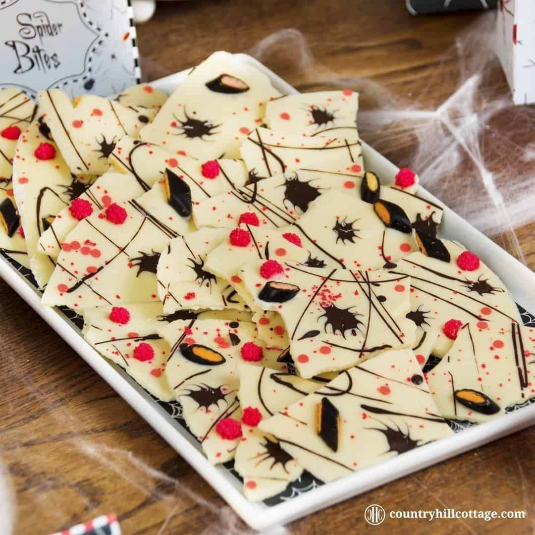 No spells are needed to make Creepy Crawler Chocolate Bark, which is a fun candy bark made with white and dark chocolate, sprinkles and liquorice. You don't have to be a candy expert to make this treat. Just melt, pour, and decorate away. Easy. You can serve the candy bark for a Halloween party or package it in cellophane bags to gift and hand out to trick-or-treaters. #chocolatebark #candybark #chocolate #Halloween | countryhillcottage.com