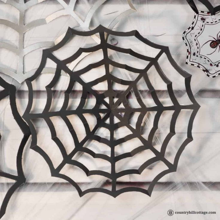 Paper spider webs add super spooky vibes to your home or classroom! DIY cobwebs look great as wall ornament, front door or window ornament, party décor and photo backdrop. All you need for this Halloween craft is paper, pencils, and craft scissors. This is a great DIY project to make with kids and an easy teacher Halloween craft for the classroom. Included are a free printable template and instructions. #DIY #spiderweb #Halloween #papercrafts   countryhillcottage.com