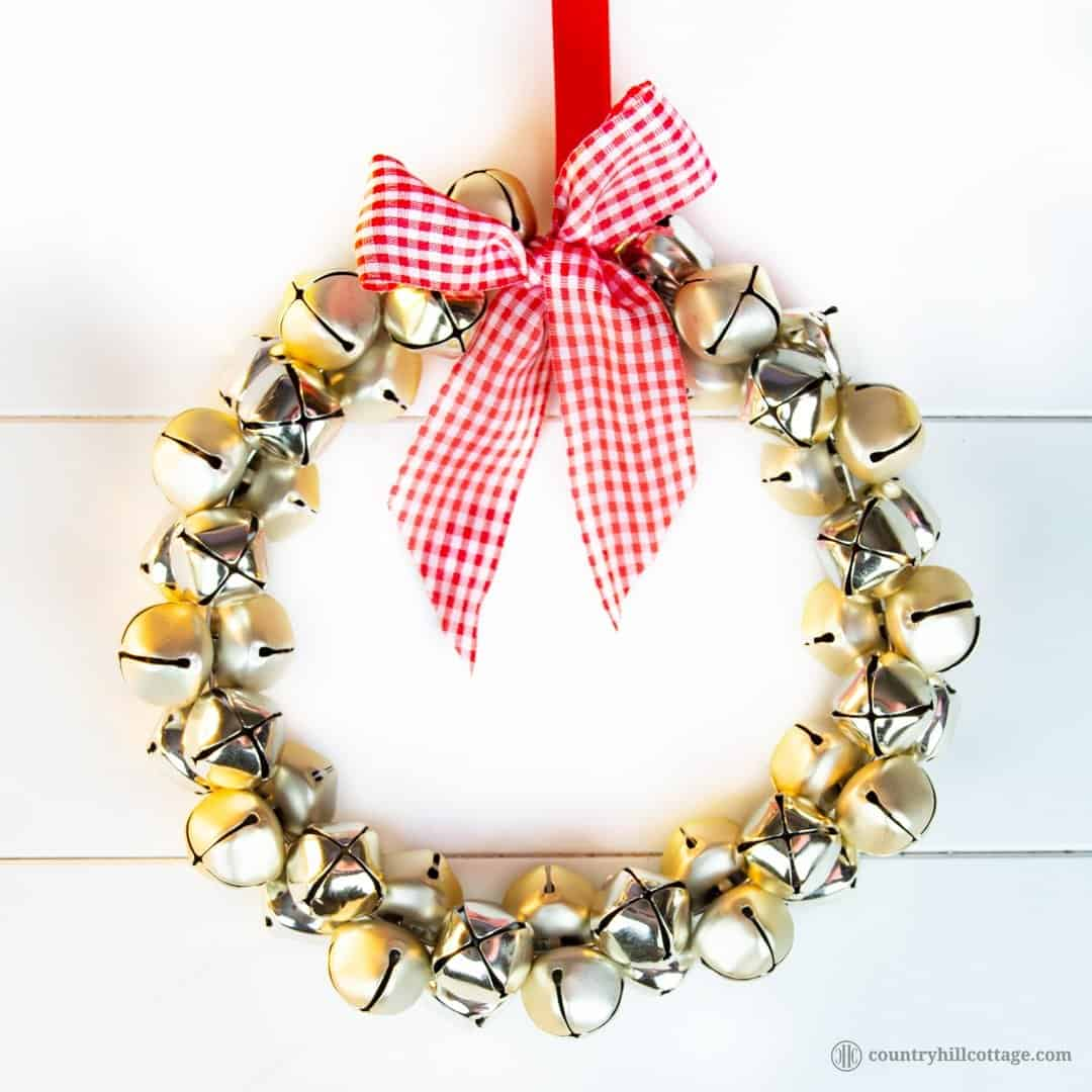 Show off your festive spirit and learn to make an easy and quick jingle bell wreath. This pretty DIY Christmas wreath adds festive touches to your front door, mantle or party décor! You only need a handful of bells, a piece of sturdy wire, ribbon and not more than five minutes to create this beautiful homemade craft holiday wreath. You can use the jingle bells wreath as Christmas door decoration or wall ornament. #wreath #ChristmasWreath #HolidayWreath #Christmas | countryhillcottage.com