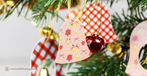 DIY paper Christmas ornaments are quick and easy Christmas craft that will bring festive charm to your home. If you need some new holiday décor, this DIY project is super simple. You only need our printable bell ornaments, scissors, ribbon, and a glue stick and a few minutes to create this pretty holiday DIY. Use these DIY ornaments to decorate your Christmas tree and house, for gift wrapping and as name tags. #gifttags #Christmas #ornaments #printables #jinglebells | countryhillcottage.com
