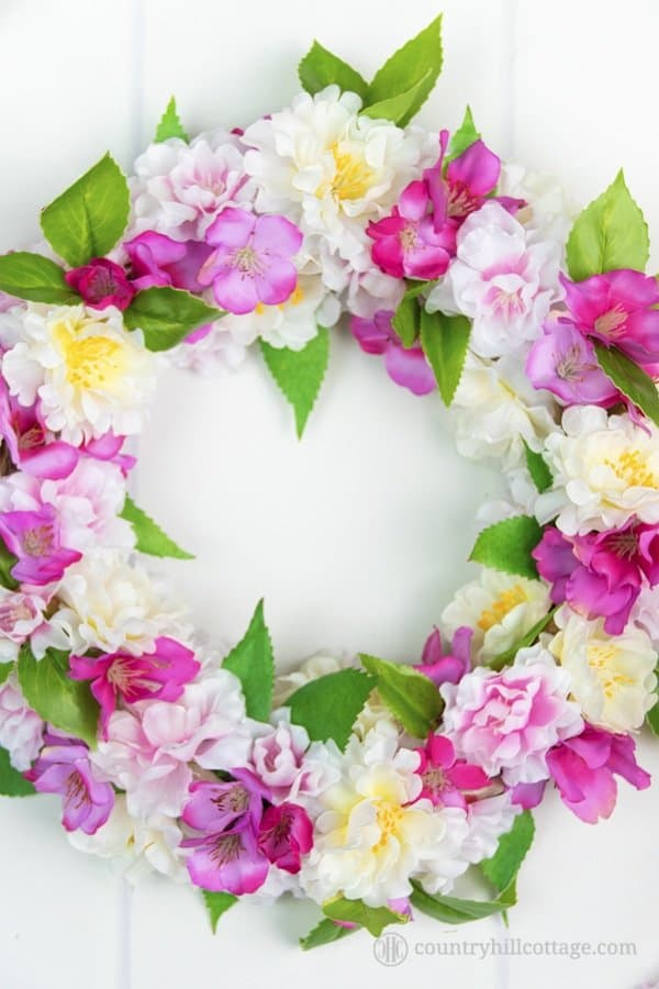 A tutorial on how to create a stunning DIY silk flower wreath with spring blossoms. Fire up your hot glue gun, grab yourself a wreath form and a bunch of silk blossoms and craft yourself to spring galore. This adorable faux flower wreath brings instant spring flair to your home and lasts season after season. You can use the blossom wreath to brighten up your front door, use it as a table topper, or give it to a friend. #silkflowers #fauxflowers #wreath #blossomwreath | countryhillcottage.com
