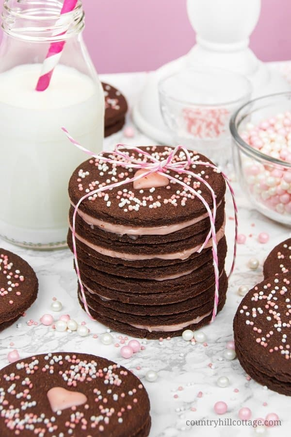 Chocolate cutout cookies with rose ganache. Flowery rose ganache, sandwiched between deliciously rich chocolate cookies, decorated with cute sprinkles. This easy no chill chocolate cutout cookie recipe is made with cocoa and melted chocolate. Rose essential oil gives the ganache a fragrant flavour. These cookies are great food gifts for Valentine's and Mother's Day, or when you crave a tasty chocolate cookie. #cutoutcookies #chocolatecookies #cookies #chocolate #ganache | countryhillcottage.com