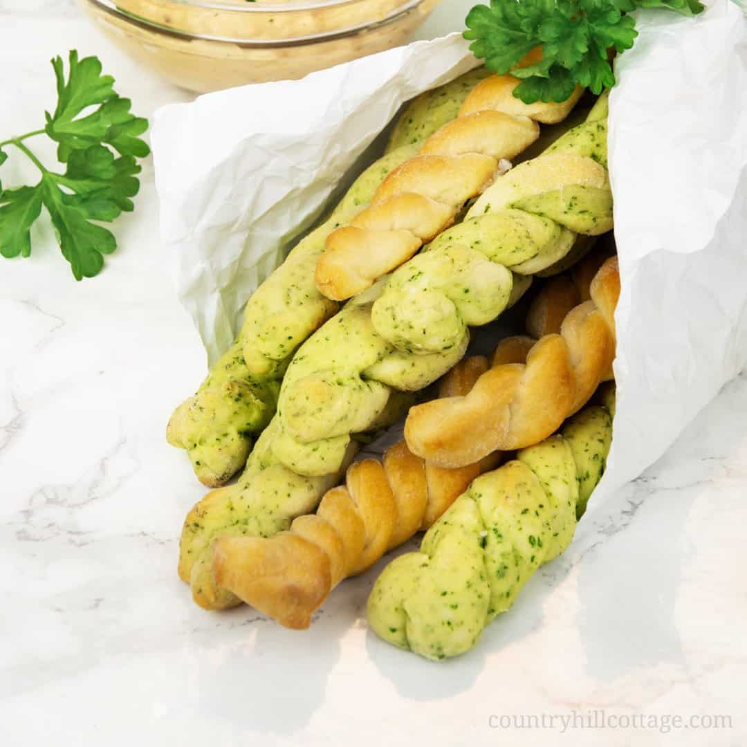 Homemade parsley braided bread sticks are soft and chewy and have a delicious, salty-herbal flavour. They're made with a yeast dough, similar to classic dinner rolls, and go excellent with warm butter or a spicy dip. Seasoned with fresh parsley, Parmigiano Reggiano,  and sea salt, it's a crowd-pleasing treat for any occasion. The bread sticks are a delicious snack, and can be served as appetizer. #breadsticks #braidedbreadsticks #appetizer #snack #partyfood  countryhillcottage.com