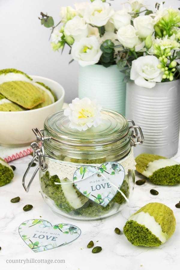 """Use these printable """"made with love"""" heart-shaped labels to gift your homemade food gifts and DIY presents. We used to package yummy pistachio lime matcha madeleines. Home baked goods are always a lovely gift, and every lover will appreciate these biscuits! I put a couple of them into a cute clip-top jar, which I decorated with a lace ribbon and a cute printable label. Tap to get the recipe and free printable gifts tags. #freebie #printable #gifttag #homemade #foodgift   countryhillcottage.com"""