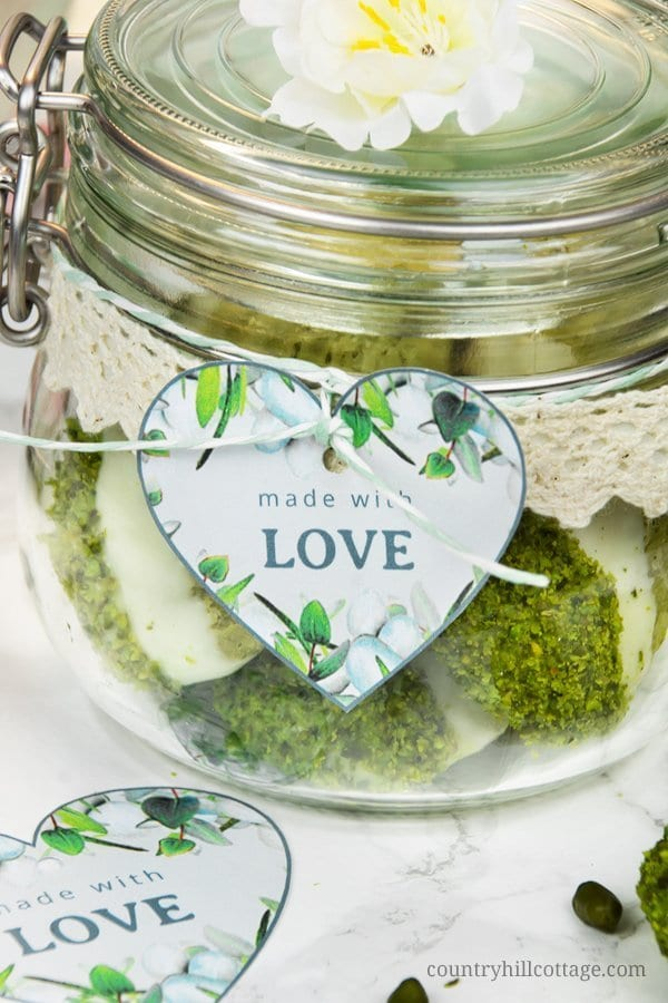 "Use these printable ""made with love"" heart-shaped labels to gift your homemade food gifts and DIY presents. We used to package yummy pistachio lime matcha madeleines. Home baked goods are always a lovely gift, and every lover will appreciate these biscuits! I put a couple of them into a cute clip-top jar, which I decorated with a lace ribbon and a cute printable label. Tap to get the recipe and free printable gifts tags. #freebie #printable #gifttag #homemade #foodgift 