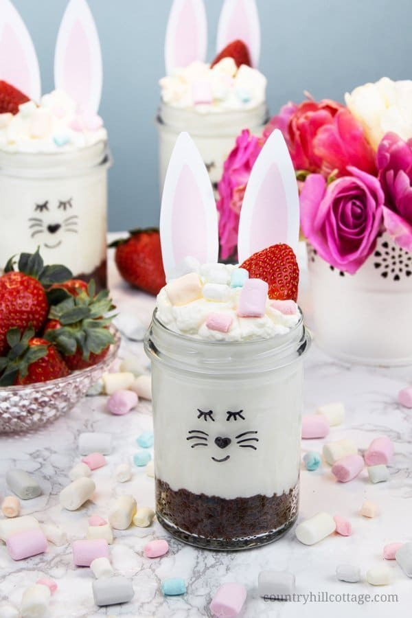 No-Bake Cheesecake Mousse Dessert Jars are made with a crunchy cookie crust, a creamy cheesecake mousse, and garnished with berries and pastel mini marshmallows. It only takes a few minutes to prepare this cheesecake dessert. We show how to turn this treat into a cute Easter dessert, perfect for Easter brunch and family get-togethers. The free printable bunny ears are available on our blog. #Easter #EasterDessert #nobake #cheesecake #mousse #dessert | countryhillcottage.com