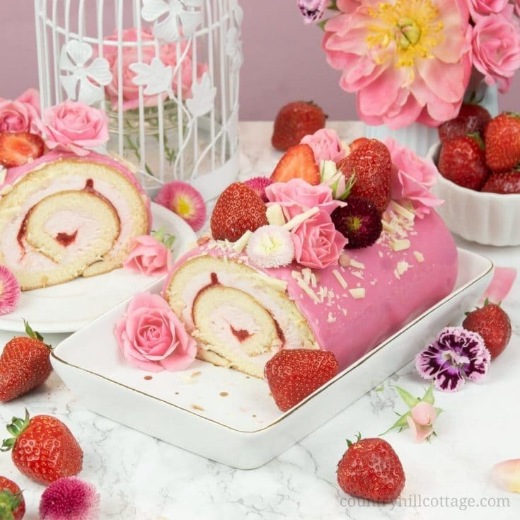 This easy strawberry roll cake recipe features soft sponge cake, a fluffy strawberry cream cheese and whipped cream filling, enrobed by shiny mirror glaze and with fresh berries and flowers as decoration. Whether you call this tasty dessert strawberry cake roll, strawberry Swiss roll, or strawberry roulade, this sweet treat tastes delicious and is perfect for entertaining guests. Strawberry Swiss Roll | Strawberry Roulade #strawberry #rollcake #swissroll #mirrorglaze| countryhillcottage.com