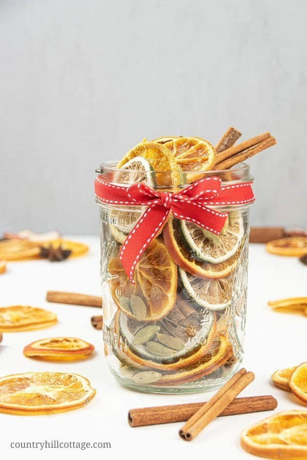 A refreshing citrus and orange potpourri! This stovetop potpourri gift is made with dried oranges and cinnamon sticks. The combination of citrus and spices is perfect to deodorize your home naturally and clean the air of stale or bad smells. How to make a DIY stovetop potpourri gift! Simmer potpourris make your house smell like Christmas and dry potpourri recipes are wonderful homemade holiday gift ideas. #holidays #potpourri #airfreshener #stovetoppotpourri #simmerpot | countryhillcottage.com