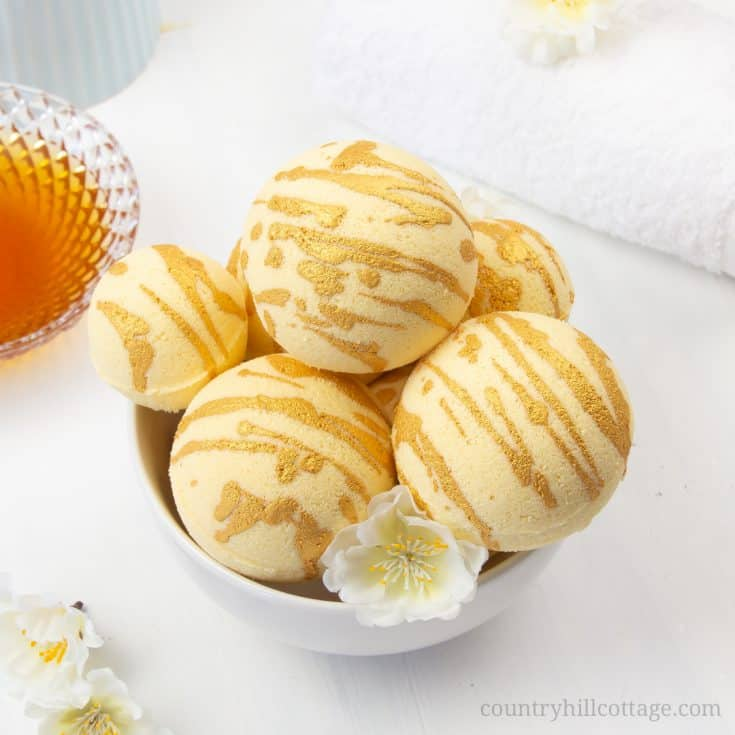 Enjoy a hydrating bath with these relaxing DIY moisturising bath bombs! The easy and natural bath bomb recipe, made with cocoa butter, milk powder, honey powder, and scented essential oils, will leave your skin supple and soft. Homemade milk and honey bath fizzies to improve skin health and improve the beauty of the skin. Learn how to make DIY bath bombs without cornstarch. #bathfizzy #milkbath #bathbomb #DIYbathbomb #DIYbeauty #DIYbath #lushbathbomb #essentialoils | CountryHillCottage.com