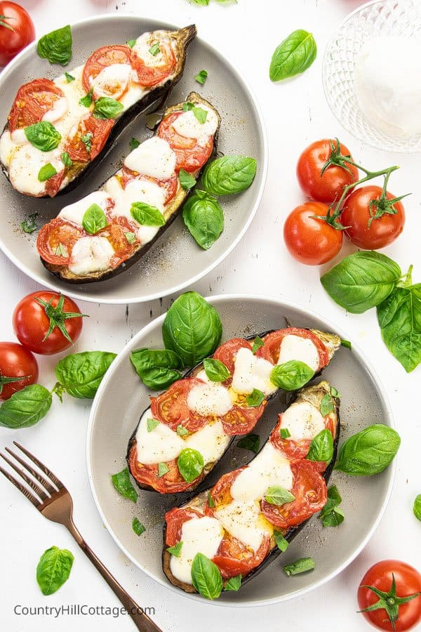 Dinner table with two baked eggplant servings