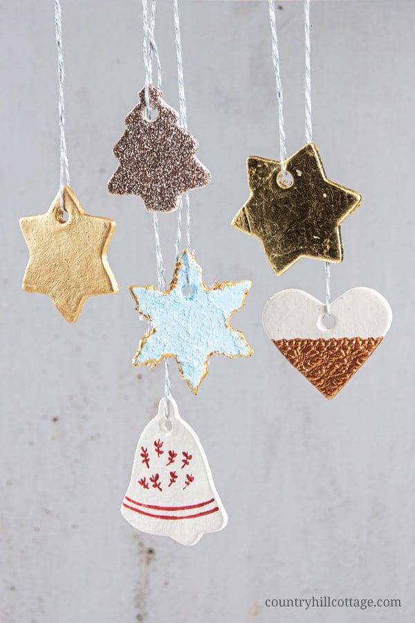 Festliche lufttrockene Lehmweihnachtsverzierungsideen! Hausgemachte Ton Ornamente sind schöne und einfache DIY Ausstecher Ornamente und ein einfaches Winterhandwerk. In diesem Schritt-für-Schritt-Tutorial mit Bildern lernen Sie, wie Sie Ornamente wie vintage bemalte Schneeflocken, rustikale Jingle Bells und wunderschöne Glitzersterne herstellen. Sie können DIY Weihnachtsschmuck als Geschenke und Baumschmuck verwenden. Ideal für Kinder und Klassenzimmer! #christmasornaments #homemade #ornaments #holidays | countryhillcottage.com