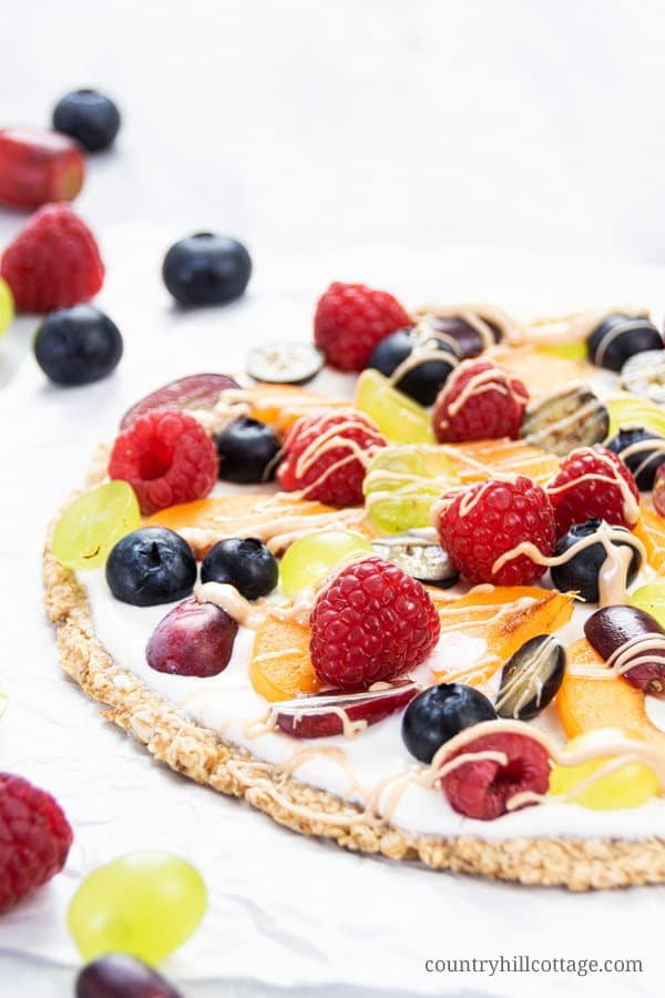 How to make the best easy healthy fruit pizza recipe with a gluten free 3 ingredients oats crust, light coconut yogurt, and fresh fruity mixed berry topping with strawberries, blueberries, raspberries. A simple homemade low carb clean eating dessert pizza, under 100 calories per slice. Yummy quick vegan dairy free low calorie no sugar added without cream cheese and sugar cookie. Great for kids, crowds, parties and summer desserts! Cute as individual mini fruit pizzas! | countryhillcottage.com
