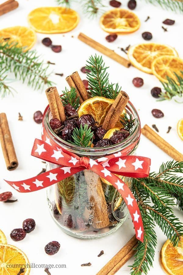 This Merry Christmas boil is the quintessential homemade holiday potpourri recipe. This dry potpourri recipe combines our favourite Christmas scents: spices, oranges, dried cranberries, and woodsy conifers. See how to make a DIY stovetop potpourri gift! Simmer potpourris and dry potpourri recipes are wonderful homemade holiday gift ideas. Includes free printable labels. #holidaygift #diygift #christmas #potpourri #airfreshener #stovetoppotpourri #simmerpot | countryhillcottage.com