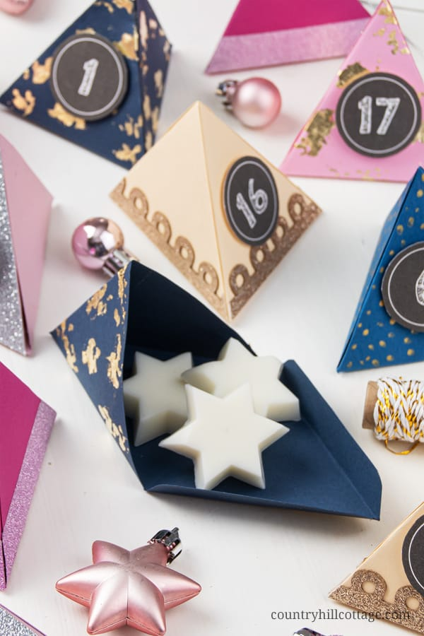 Make your own easy DIY paper advent calendar with free printable templates for the boxes numbers! This homemade advent calendar is a fun Christmas papercraft and holiday gift for kids, adults, husband, boyfriend, teens, children. The tutorial includes handmade advent calendar fillers ideas like chocolate and beauty items for what to put in. The design cane me modern or traditional and comes with PDF and SVG templates. #adventcalendar #papercrafts #DIY #holidaycrafts   countryhillcottage.com
