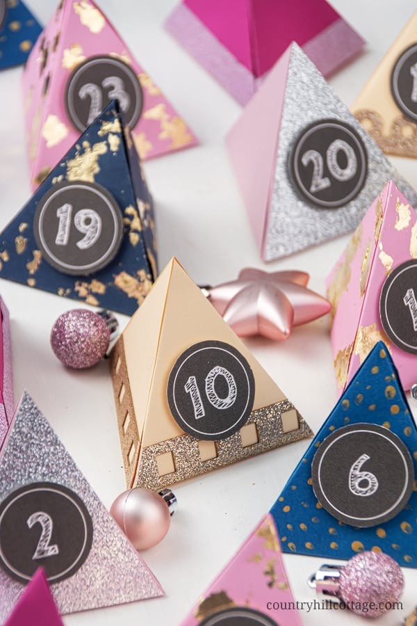 Make your own easy DIY paper advent calendar with free printable templates for the boxes numbers! This homemade advent calendar is a fun Christmas papercraft and holiday gift for kids, adults, husband, boyfriend, teens, children. The tutorial includes handmade advent calendar fillers ideas like chocolate and beauty items for what to put in. The design cane me modern or traditional and comes with PDF and SVG templates. #adventcalendar #papercrafts #DIY #holidaycrafts | countryhillcottage.com