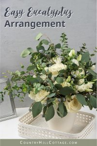 See how to make an easy and modern DIY eucalyptus arrangement in a vase! This homemade fresh flower design is made with different types of eucalyptus, including silver dollar, baby blue and seeded, and stunning white flowers. The simple large vase arrangement is beautiful as farmhouse home decor and could also be transformed into tall wedding center pieces for receptions. The step-by-step tutorial also includes tips for faux/fake and dry greenery. #eucalyptus #homedecor  countryhillcottage.com