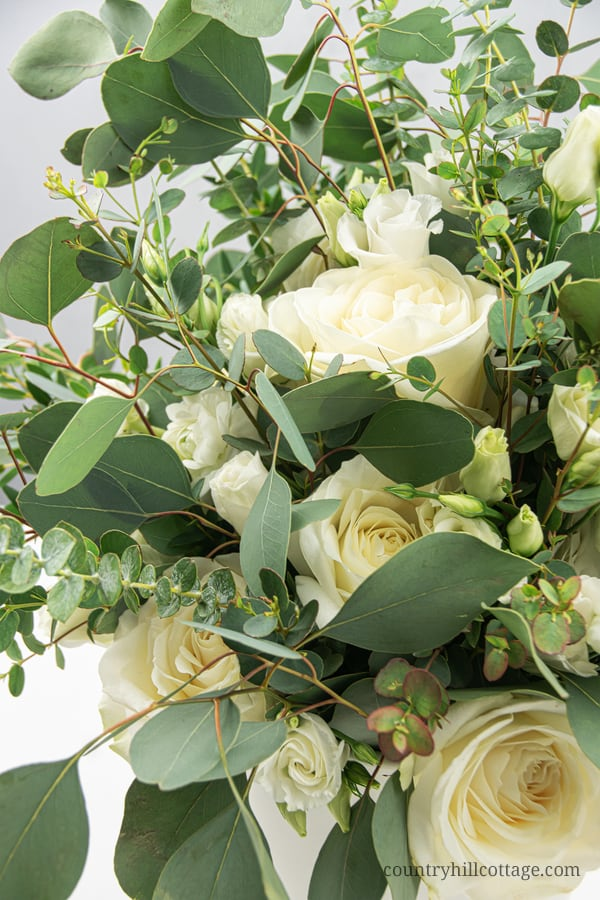 See how to make an easy and modern DIY eucalyptus arrangement in a vase! This homemade fresh flower design is made with different types of eucalyptus, including silver dollar, baby blue and seeded, and stunning white flowers. The simple large vase arrangement is beautiful as farmhouse home decor and could also be transformed into tall wedding center pieces for receptions. The step-by-step tutorial also includes tips for faux/fake and dry greenery. #eucalyptus #homedecor| countryhillcottage.com