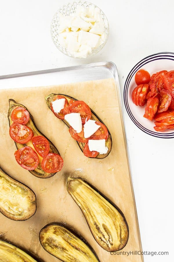Arranging tomatoes and mozzarella cheese on baked eggplants