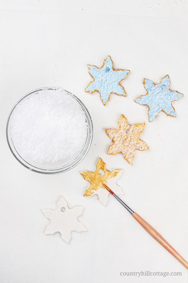 Holiday Snowflake Ornaments with artificial snow! Homemade clay ornaments are beautiful and easy DIY cookie cutter ornaments and a simple winter craft. In this step-by-step tutorial with pictures, you'll learn how to make ornaments like vintage painted snowflakes, rustic farmhouse jingle bells and beautiful glitter stars. You can use DIY Christmas ornaments as gifts and tree decorations. Great for kids and classroom! #christmasornaments #homemade #ornaments #holidays | countryhillcottage.com