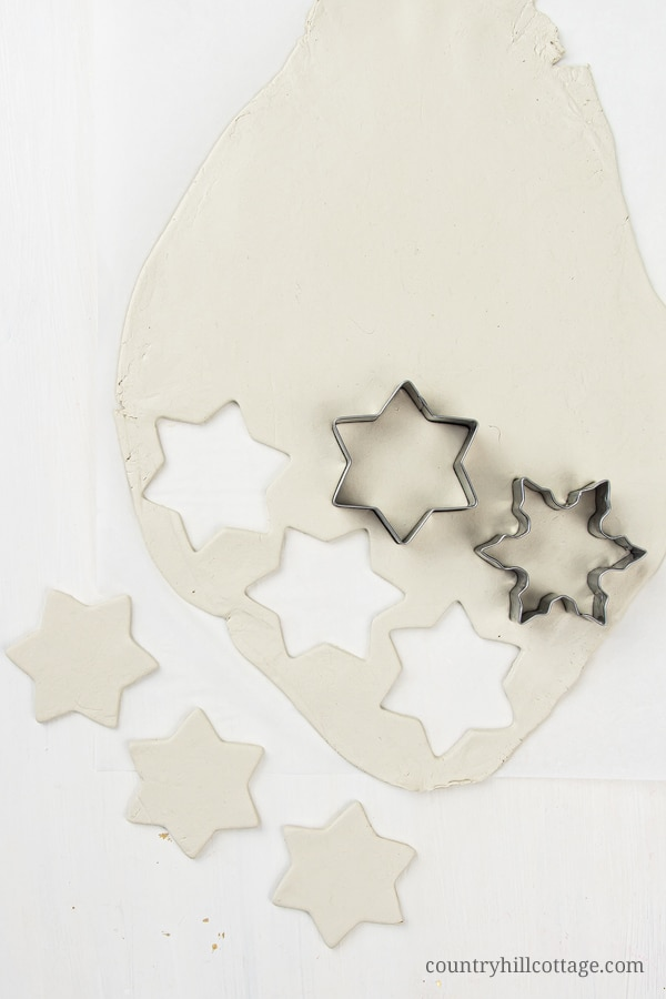 How to make homemade clay holiday ornaments: Cut out clay Christmas decorations using Christmas cookie cutters and poke hole for hanging with drinking straw. In this step-by-step tutorial with pictures, you'll learn how to make ornaments like vintage painted snowflakes, rustic farmhouse jingle bells and beautiful glitter stars. You can use DIY Christmas ornaments as gifts and tree decorations. Great for kids and classroom! #clay #christmasornaments #ornaments | countryhillcottage.com