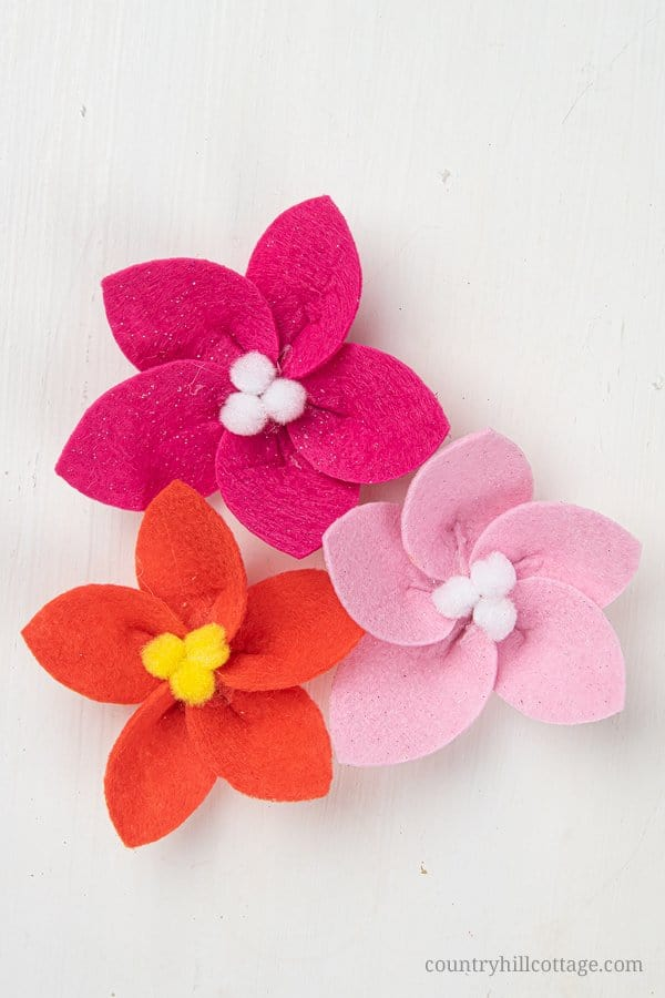 How to make a felt poinsettia – Easy DIY felt flower tutorial for Christmas and the holidays. See how to make a festive DIY Christmas felt wreath! Creating your own homemade Christmas wreath with felt is super easy and fun. This handmade holiday felt craft comes with free printable pattern templates and SVG files for Cricut. Great for decorations, jewelry, craft projects. #felt #feltflowers #feltflowerwreath #poinsettia #feltcraft | countryhillcottage.com