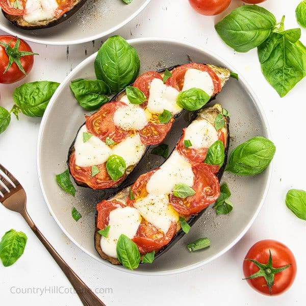 Roasted aubergine with tomatoes and cheese on a plate