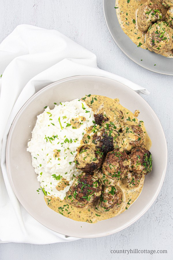 How to make gluten-free KETO Swedish meatballs from scratch! Light low carb meatballs with ground beef in creamy gravy sauce are a quick easy meal or dinner, tastes authentic and traditional. The homemade Ikea copycat recipe can be made on the stovetop, slow cooker, Crockpot or Instant Pot. Can be stored frozen. What to serve with: zucchini noodles, pasta, cauliflower mash or rice as side dishes. #meatballs #Swedishmeatballs #keto #ketomeatballs #lowcarb #glutenfree | countryhillcottage.com