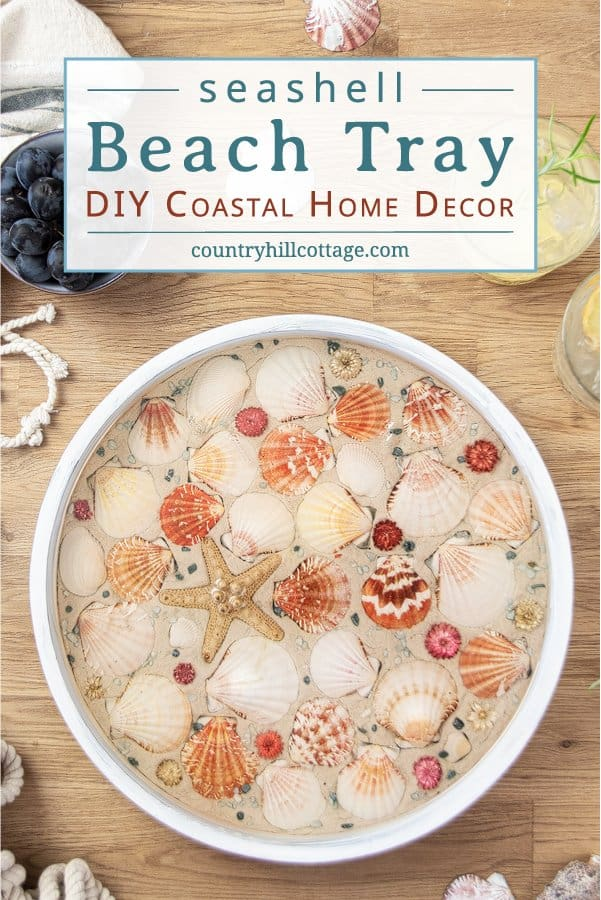 How to make a modern round wood DIY beach tray with seashells! The easy seashell craft is a fun summer craft project and rustic farmhouse coastal decor. The step-by-step makeover tutorial includes ideas for materials and working with epoxy resin to create a homemade white painted wooden seashell serving tray with gold trim! Elegant as living room decor, coffee table centerpiece, kitchen display, custom tea tablet, or outdoor party. #servingtray #tray #homedecor #coastal| CountryHillCottage.com
