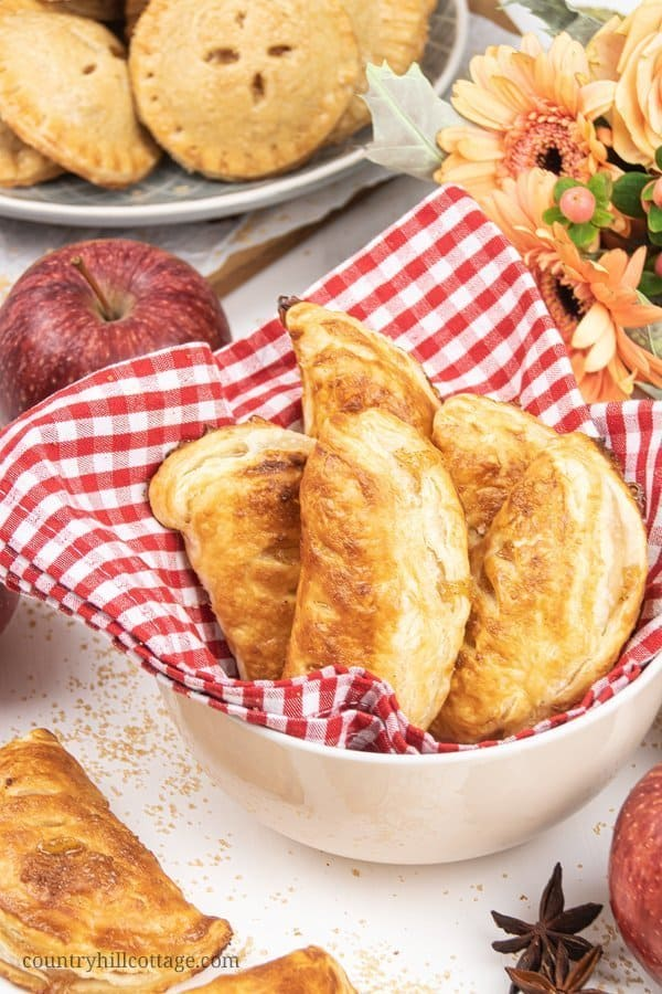 Delicious baked apple hand pies with puff pastry are quick and easy! See how to make homemade apple turnovers with a flavorful caramel apple filling. The apple recipe can also be made with Pillsbury crescent rolls or phyllo sheets. A delicious breakfast, snack and dessert. #appelturnovers #turnovers #applehandpie   countryhillcottage.com