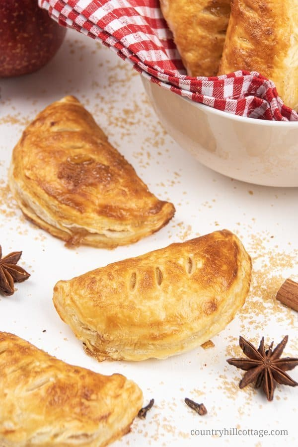Delicious baked apple hand pies with puff pastry are quick and easy! See how to make homemade apple turnovers with a flavorful caramel apple filling. The apple recipe can also be made with Pillsbury crescent rolls or phyllo sheets. A delicious breakfast, snack and dessert. #appelturnovers #turnovers #applehandpie | countryhillcottage.com